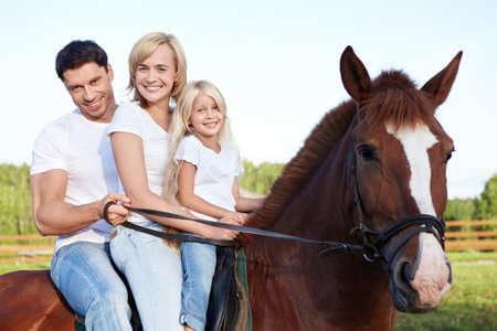 mujer en caballo: Familia atractiva en un caballo marr�n Foto de archivo