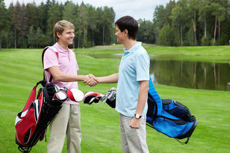 rivals: Rivals shake hands on the golf course Stock Photo