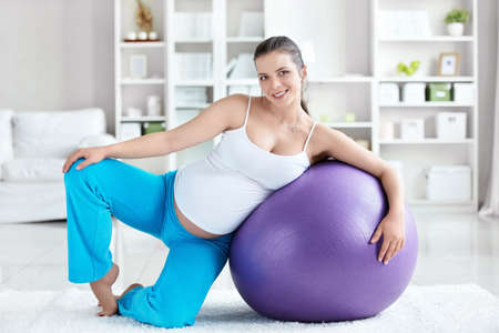 A pregnant woman with a ball at home photo