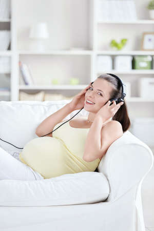 Pregnant woman with headphones at home photo