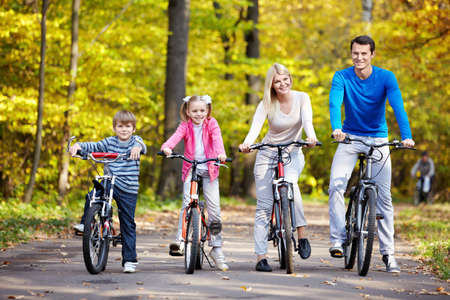 Family on bikes in the park in autumn photo