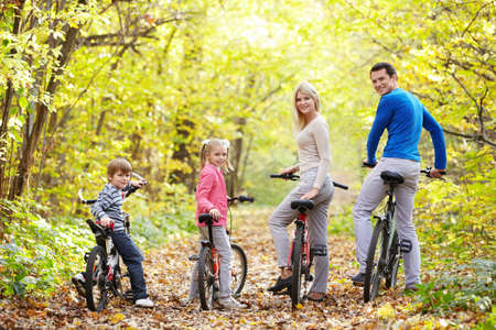 recreational vehicle: Family on bikes in the park in autumn