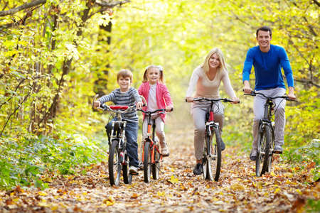 family park: Family on bikes in the park in autumn