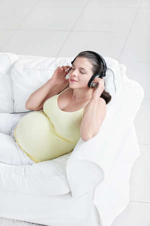 Young pregnant woman with headphones photo