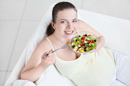 Young pregnant woman eating salad photo