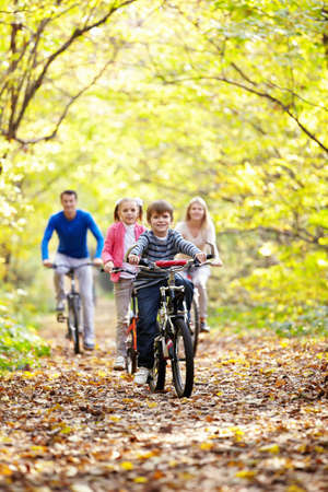 woman exercising: A young family with children on bicycles Stock Photo