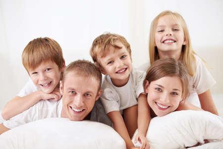 familia abrazo: Familia feliz con los ni�os en la cama Foto de archivo