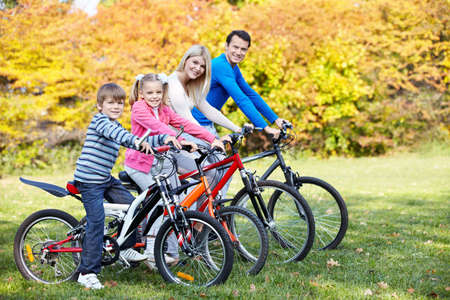 exercising: Family with children on bikes in the park