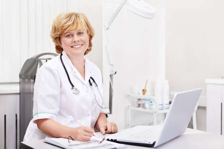 doctor computer: Doctor smiling at the workplace Stock Photo