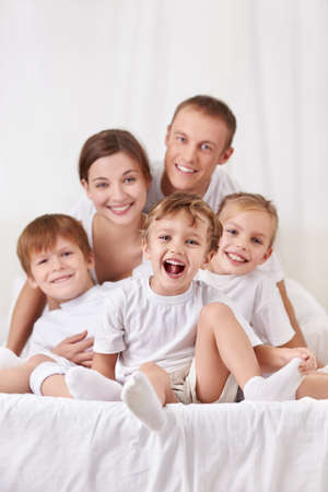 Happy family with children in the bedroom photo