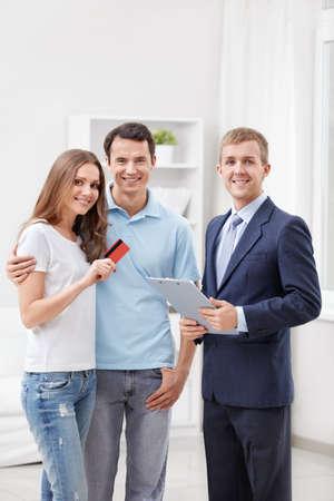 Consultor y una pareja con tarjeta de cr�dito Foto de archivo - 12435669