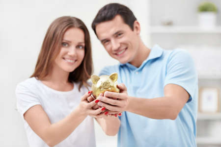 finance girl: Young couple holding hands in the piggy bank Stock Photo