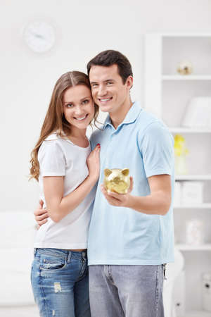 Young couple holding hands in the piggy bank photo