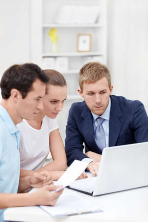The consultant and the young couple for a laptop Stock Photo - 12435571