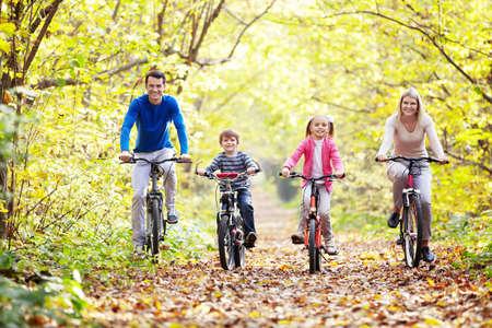 Het gezin in het park op de fiets