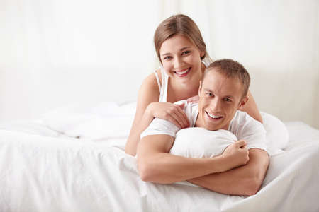 Laughing couple in bedroom photo