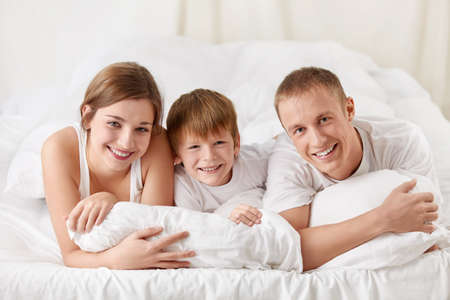 Smiling family with a child in the bedroom photo