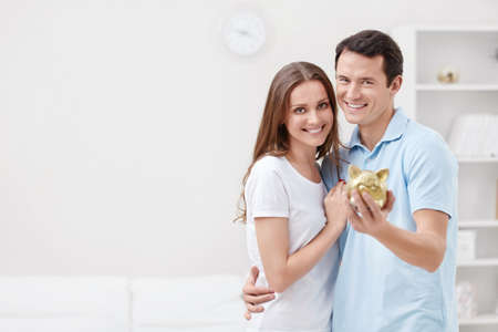 finance girl: Young couple with piggy bank Stock Photo