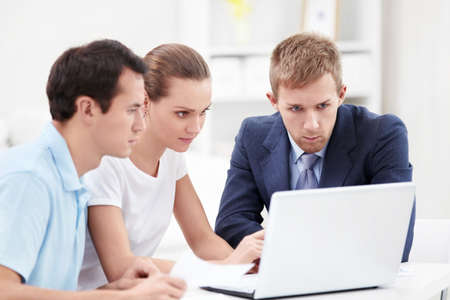 insurance consultant: Consultant and a couple looking at laptop Stock Photo