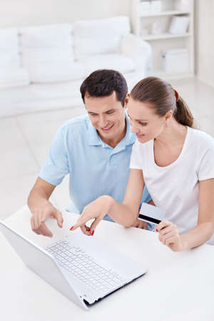 finance girl: A young couple with a credit card in the laptop looks