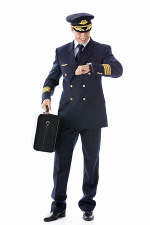 A pilot with a suitcase looking at the clock on a white background photo