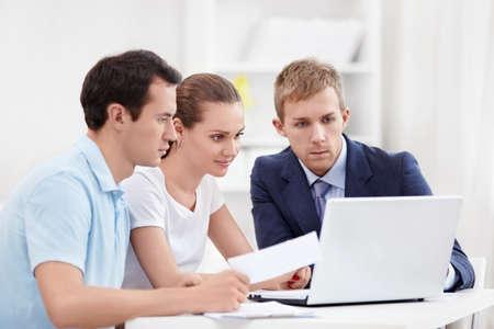 Consultor con una pareja que busca en la computadora port�til Foto de archivo - 12773582