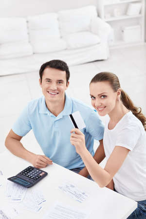 A young couple with a credit card at home photo