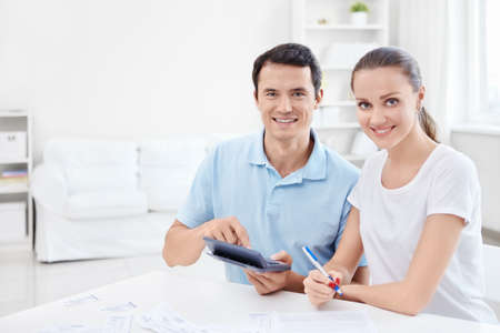 Man and woman with a calculator at home photo