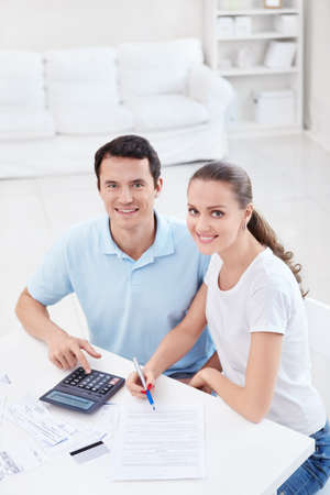 Young couple with a calculator at home photo