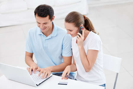 Young couple with laptop and phone Stock Photo - 12773497