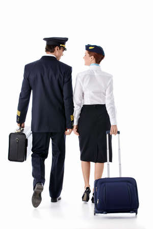 The pilot and stewardess with a suitcase on a white background photo
