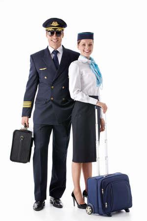 azafata: El piloto y la azafata con una maleta en un fondo blanco Foto de archivo