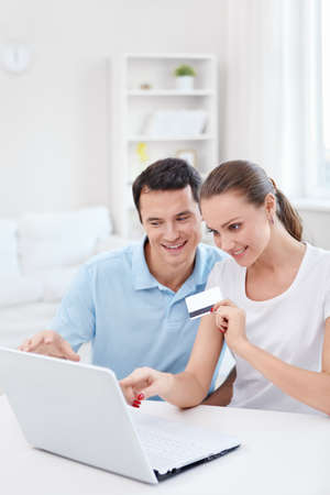 Young couple with laptop and credit card at home photo