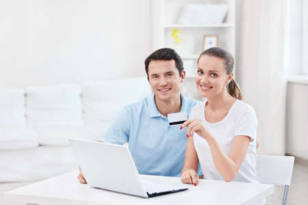 Young couple with laptop and credit card at home Stock Photo - 12928780