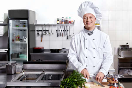 chefs whites: Cook cut vegetables in the kitchen Stock Photo