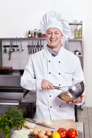 chefs whites: A cook prepares in the kitchen Stock Photo