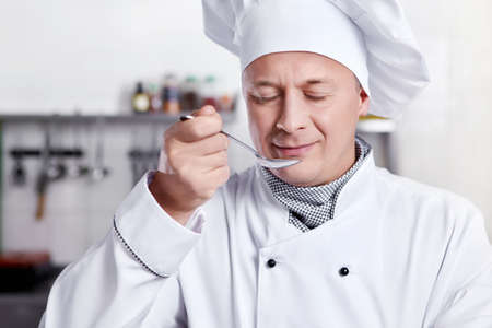 chefs whites: Mature cook prepares in the kitchen