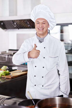 chefs whites: Smiling chef in the kitchen Stock Photo