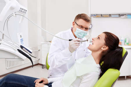 The dentist treats teeth of the patient in the clinic photo