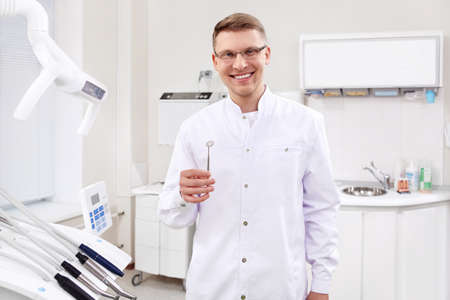 A young dentist with instruments in the clinic photo