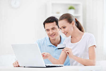 A couple with a credit card and a laptop at home photo