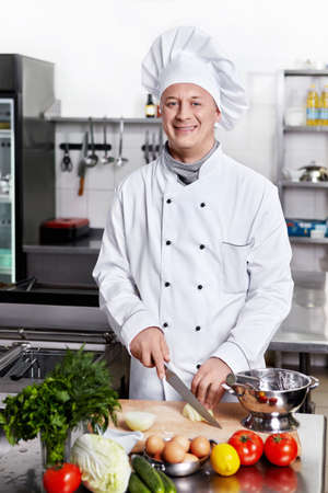 chefs whites: Smiling chef prepares in the kitchen