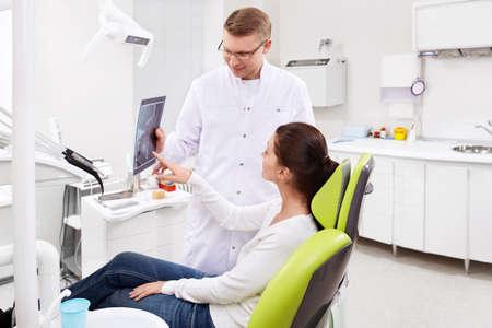uniformes de oficina: El m�dico indica al paciente a los rayos X en la cl�nica dental