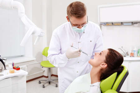The doctor treats the patient to the teeth in the dental clinic photo