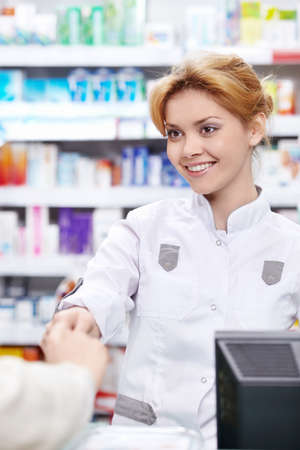 The pharmacist sells the medicine in a pharmacy photo