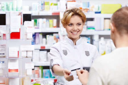 The pharmacist sells the medicine in a pharmacy Stock Photo