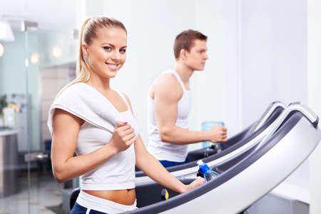 atleta corriendo: Chica joven y un hombre en el gimnasio