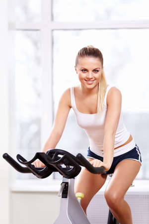 Smiling woman on a bicycle simulator Stock Photo