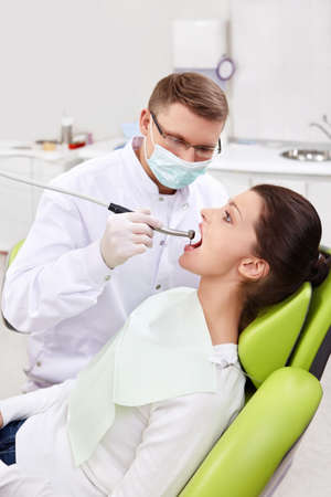 The dentist treats teeth of patient photo