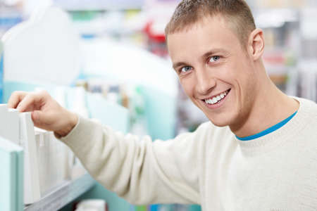 Smiling man at the pharmacy shelves Stock Photo - 13709731